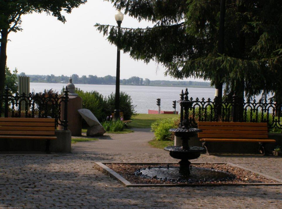 A view of the St. Lawrence River with walkway, fountain and bench in foreground